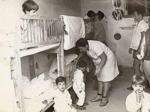 תמונה ישנה בשחור-לבן. ילדי הקיבוץ במיטות קומותיים